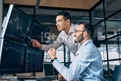 Two men traders sitting at desk at office together monitoring stocks data candle charts on screen analyzing price flow smiling cheerful having profit teamwork concept