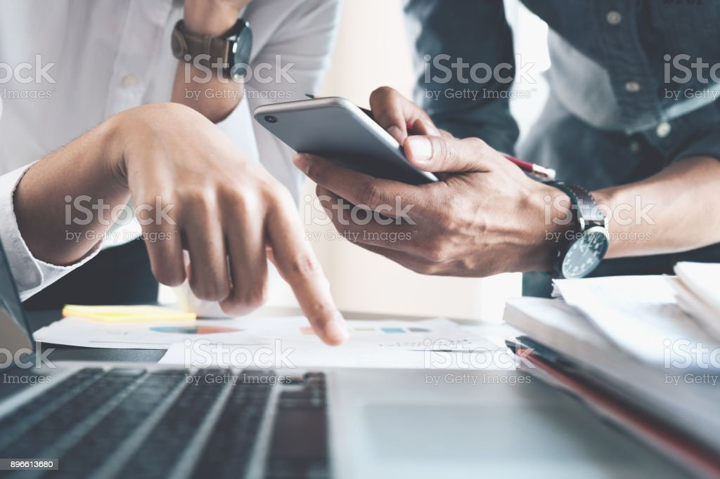 Teamwork concept. Young businesswoman hand holding a smartphone for discuss business strategy with businessman, laptop computer, many document on table in office. stock photo