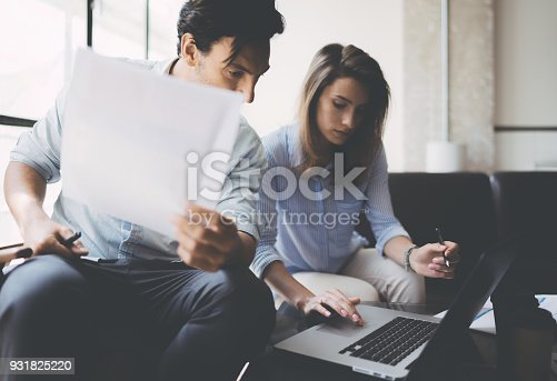912617272 istock photo Teamwork concept.Young business people working with new startup project.Mobile devices on table,documents and marketing reports.Blurred background,flare.Horizontal. 931825220