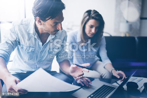 912675036istockphoto Teamwork concept.Young business people working with new startup project.Blurred background,flare.Horizontal. 912614140