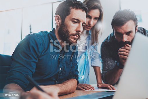 istock Teamwork concept.Young coworkers working with new business project in modern office.Group of three people analyze data on laptop computer.Horizontal,blurred background. 912677744