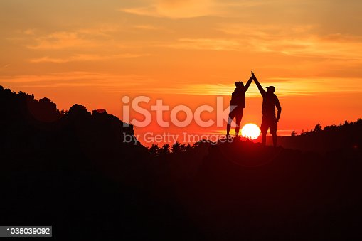 Teamwork couple celebrating silhouette in inspiring mountains sunset. Team of climbers celebrate reached goal and success. Achievement and motivation concept on top of mountain, Corsica France.
