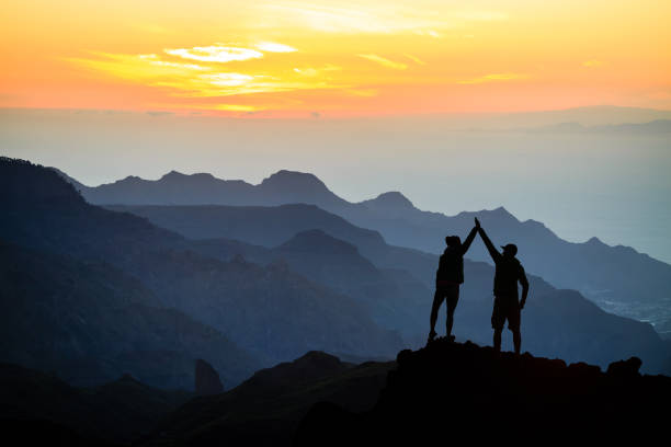 團隊合作夫婦攀爬説明手 - 山頂 個照片及圖片檔