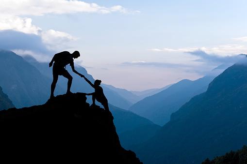 istock Teamwork couple climbing helping hand 475294806