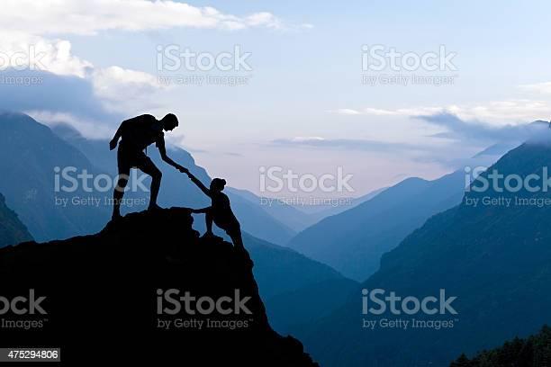 Photo of Teamwork couple climbing helping hand