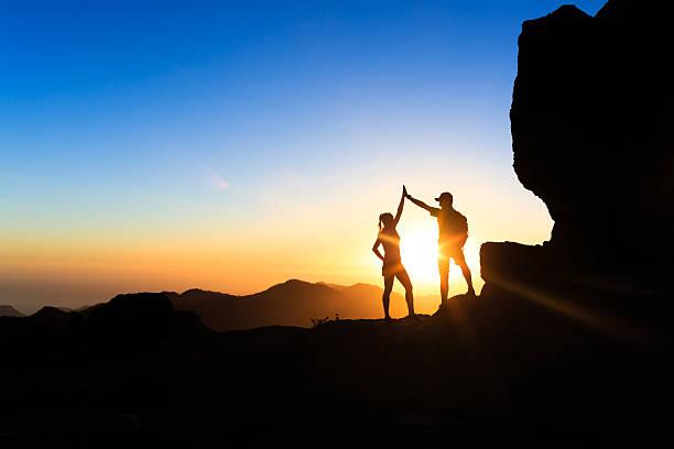 Teamwork couple climbing helping hand foto