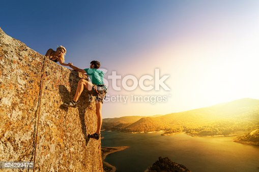 istock Teamwork couple climbing helping hand 824299472