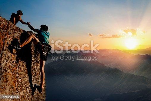 istock Teamwork couple climbing helping hand 876203400