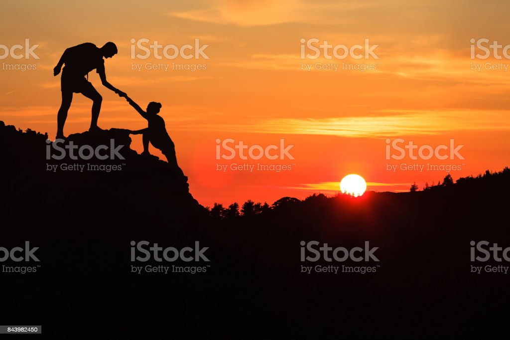 Teamwork couple helping hand trust in inspiring mountains - foto stock