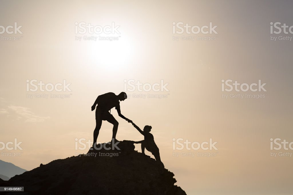 Teamwork couple helping hand trust in inspiring mountains royalty-free stock photo
