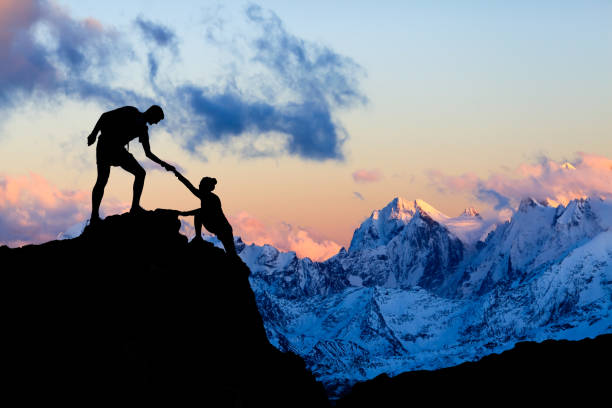 Teamwork couple helping hand, trust in mountains stock photo