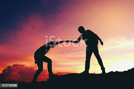 istock Teamwork couple helping hiking each other silhouette on mountains 910730596