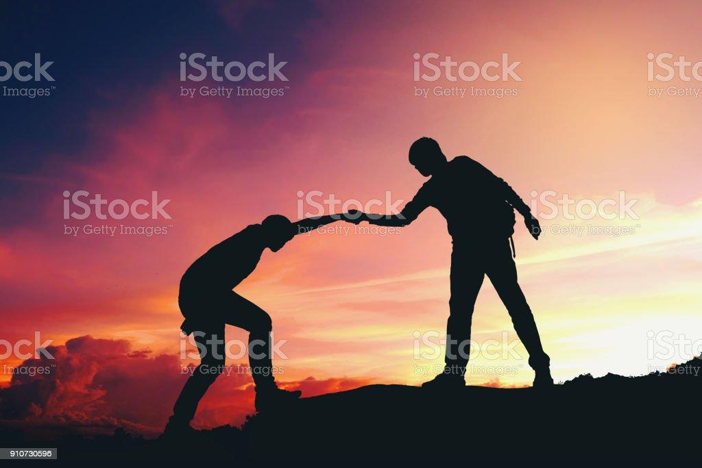 Teamarbeit-paar helfen einander Wandern silhouette auf Bergen – Foto