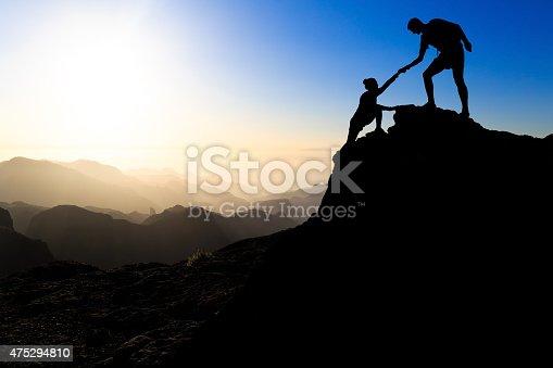 istock Teamwork couple hiking helping hand 475294810