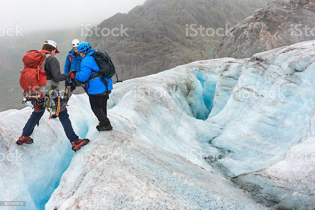 Teamwork crossing crevasses stock photo