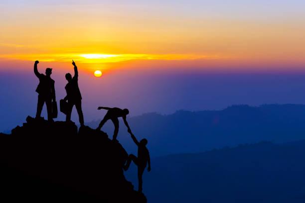 teamwork freundschaftswandern helfen sich gegenseitig treuhand-silhouette in den bergen, sonnenaufgang. teamwork von vier männer-wanderer, die sich gegenseitig auf dem bergsteigerteam schöne sonnenaufgangslandschaft helfen - trust stock-fotos und bilder