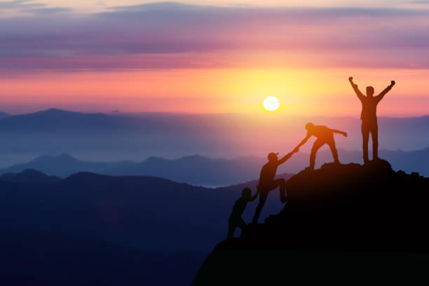 團隊友誼徒步旅行幫助對方信任援助剪影在山上,日出。兩名男子徒步旅行者團隊在登山隊山頂上互相幫助美麗的日出景觀。 - 成功 個照片及圖片檔