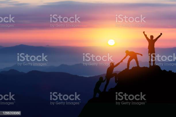 Photo of Teamwork friendship hiking help each other trust assistance silhouette in mountains, sunrise. Teamwork of two men hiker helping each other on top of mountain climbing team beautiful sunrise landscape
