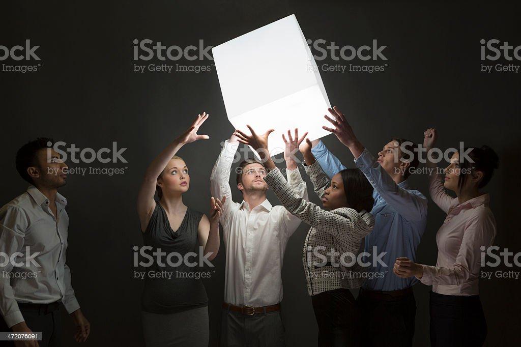Teamwork – group guide illuminated cube down th e line stock photo