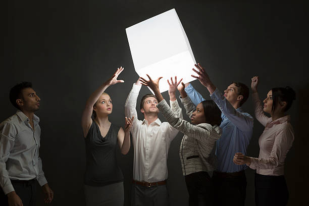 Teamwork – group guide illuminated cube down th e line stock photo