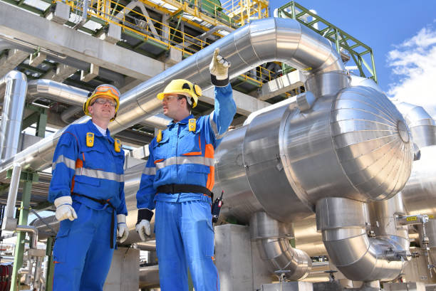 teamwork: group of industrial workers in a refinery - oil processing equipment and machinery stock photo