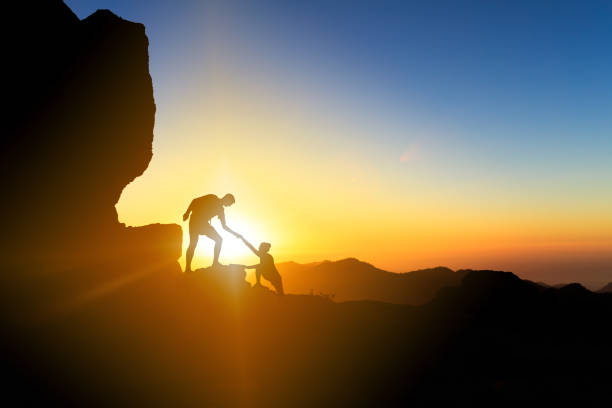 Teamwork helping hand couple climbing at sunset stock photo