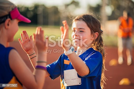 Two girls are high fiving after a difficult race in athletics club.