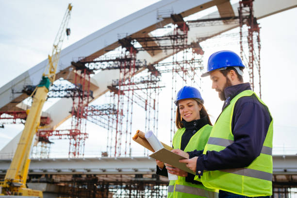 teamwork in construction industry - two engineers working together on construction site with blueprints and plans - civil engineer stock photos and pictures