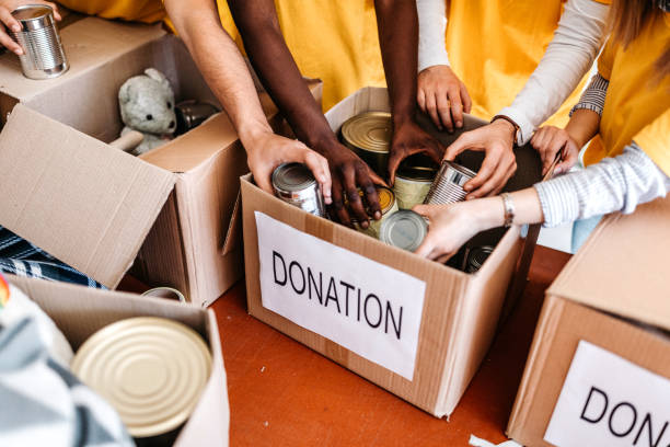 Teamwork in homeless shelter Small multi-ethnic group of people working on humanitarian aid project food drive stock pictures, royalty-free photos & images