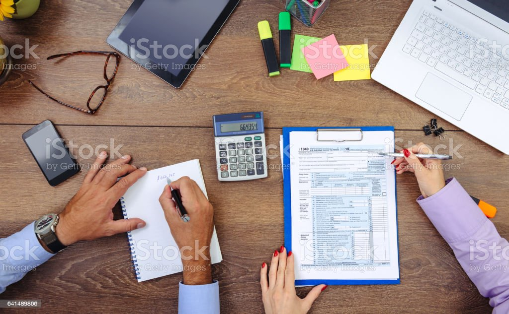 Teamwork in office - man and woman dealing with financial data, taxation and stock markets stock photo