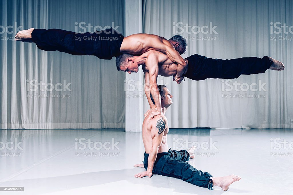 Teamwork is a succes as acrobats use strength and balance stock photo
