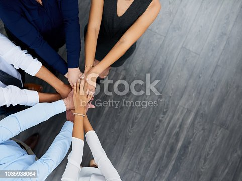 High angle shot of a group of businesspeople joining their hands together in unity