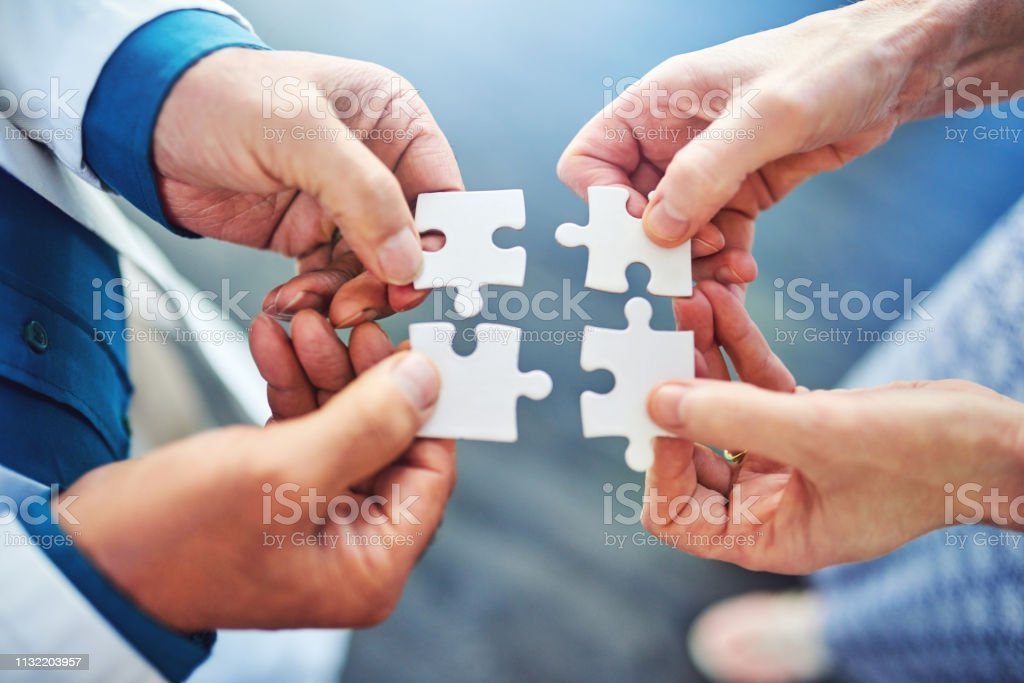 Teamwork is always the answer Cropped shot of two medical professionals connecting puzzle pieces together Adult Stock Photo