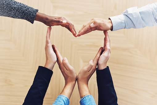 High angle shot of a group of unidentifiable businesspeople forming a heart shape with their hands