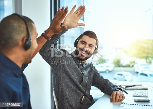 Shot of two call centre agents high fiving each other while working in an office