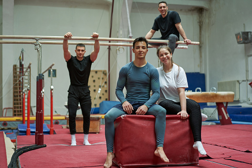 Portrait of a young group of an artistic gymnastics, training together in the indoor gymnastic court