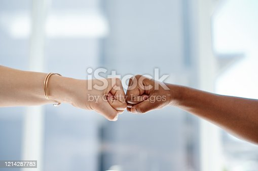 Cropped shot of two unrecognizable businesswomen fist bumping each other inside an office