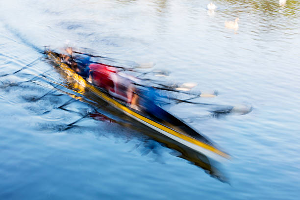 Teamwork, motion blurred rowers in rowing boat training on river - foto de stock