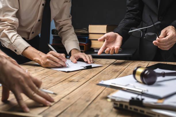 teamwork of business lawyer meeting hart on reislation in courtroom to help their customer. - rechtsassistent stock-fotos und bilder