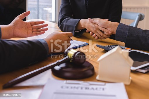 836113188 istock photo Teamwork of business legal shaking hands meeting after great meeting about Property Law in courtroom to help their customer. 1034233378
