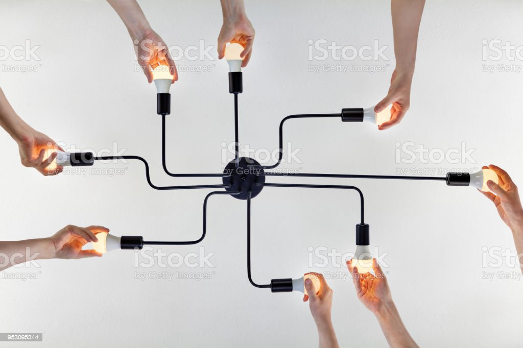 Teamwork of collective when updating LED lamps in ceiling chandelier. stock photo
