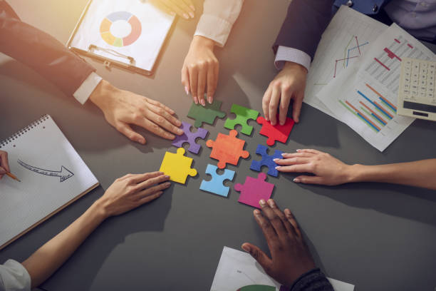 Teamwork of partners. Concept of integration and startup with puzzle pieces Businessmen working together to build a puzzle. Concept of teamwork, partnership, integration and startup. collaboration stock pictures, royalty-free photos & images