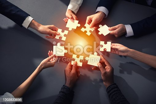 Businessmen working together to build a puzzle. Concept of teamwork, partnership, integration and startup.