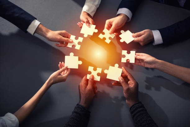 teamwork of partners. concept of integration and startup with puzzle pieces - coinvolgimento dei dipendenti foto e immagini stock