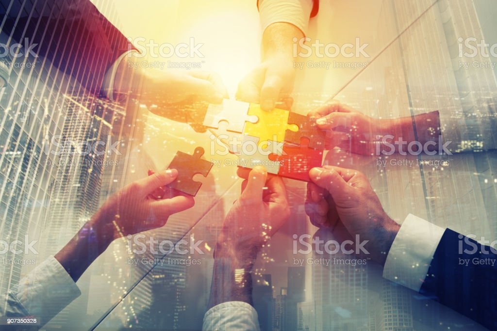 Teamwork of partners. Concept of integration and startup with puzzle pieces. double exposure - Foto stock royalty-free di Accordo d'intesa