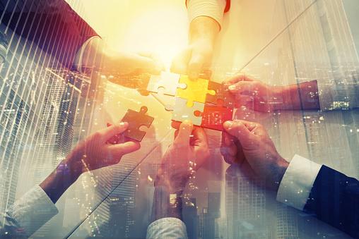 Teamwork Of Partners Concept Of Integration And Startup With Puzzle Pieces Double Exposure - Fotografie stock e altre immagini di Accordo d'intesa