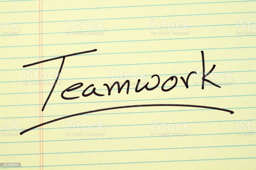 Teamwork On A Yellow Legal Pad stock photo