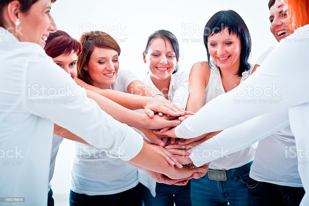 Teamwork Teamwork concept. Group of smiling women joining hands.  Adult Stock Photo