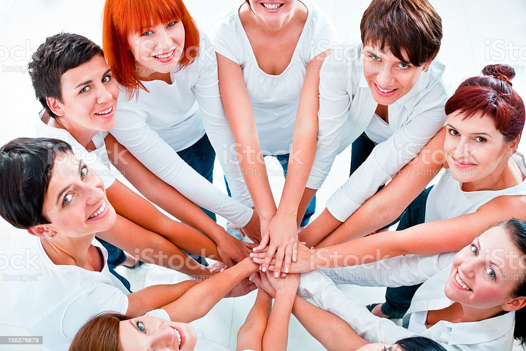 Teamwork Teamwork concept. Group of women joining hands. Elevated view, white background. Adult Stock Photo