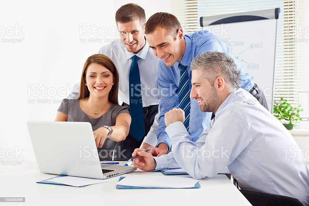 Teamwork Four business colleagues working together on laptop in the meeting room. Adult Stock Photo
